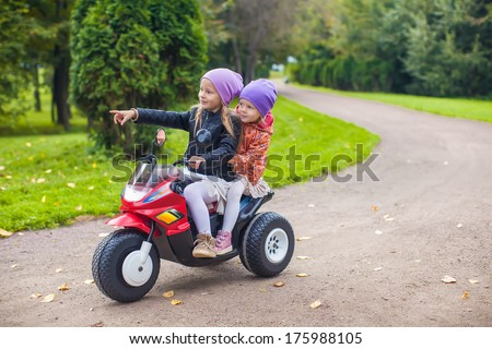 Adorable little girls riding on motobike in the green park - stock photo