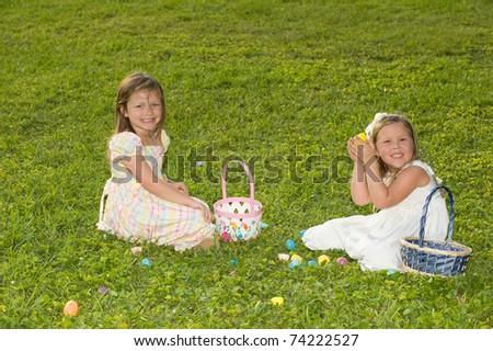 Adorable little girls sitting with Easter baskets and plastic eggs in a field - stock photo