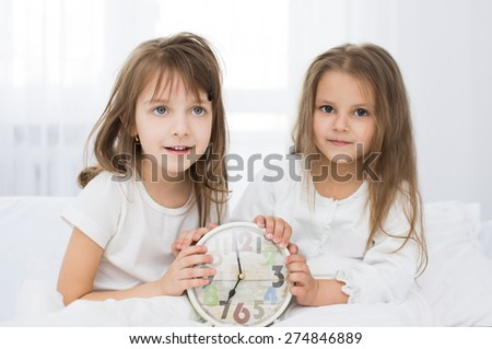 Adorable little girls wake up in the bed - stock photo