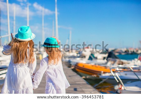 Adorable little girls walking in a port on summer day - stock photo