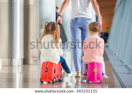 Adorable little girls with father in airport sitting on suitcase waiting for boarding - stock photo