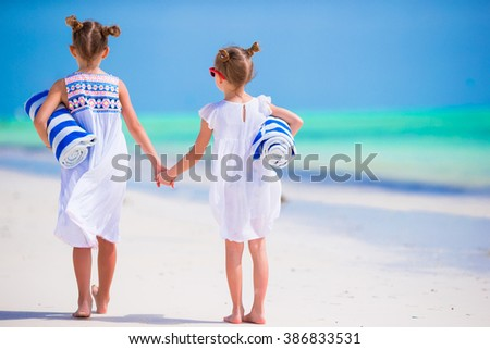 Adorable little girls with towels at tropical beach - stock photo