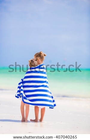 Adorable little girls wrapped in towel at tropical beach - stock photo