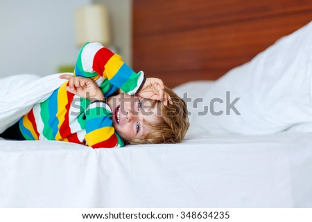 Adorable little kid boy after sleeping in his white bed in colorful pajama. Funny happy child playing and smiling. Family, vacation, childhood concept - stock photo
