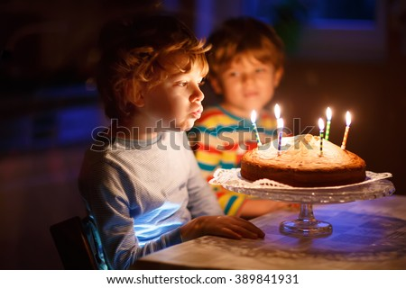 Adorable little kid boy celebrating his birthday and blowing candles on homemade baked cake, indoor. Brother on background. Birthday party for children. - stock photo