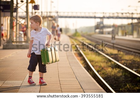 Adorable little kid boy dressed in shorts and polo t-shirt on a railway station, waiting for the train with retro old green suitcase. Ready for vacation. Young traveler on the platform. - stock photo