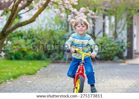 Adorable little kid boy driving his first bike or laufrad in park or garden on warm spring day. Happy child having fun. Active leisure for kids outdoors.