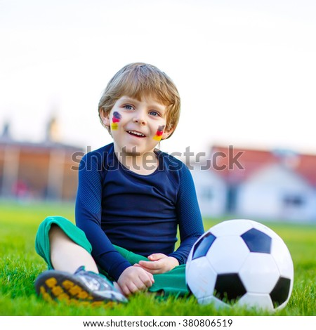 Adorable little kid boy  having fun with playing soccer with football on field, outdoors. In white German national uniform and painted German flag on face. Happy child about european championship - stock photo