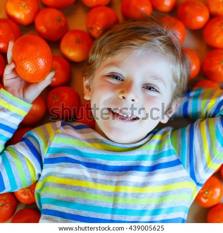 Adorable little kid boy in colorful clothes with mandarin oranges background. Happy smiling child with lot of fruits. Healthy food, eating and lifestyle concept.