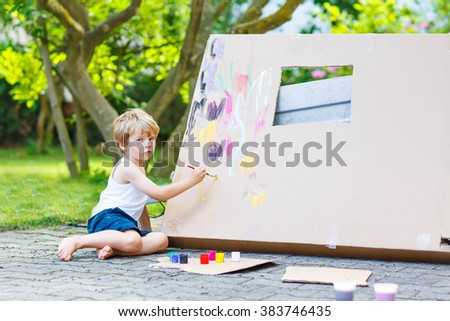 Adorable little kid boy painting big paper house with colorful paintbox. Children having fun outdoors. Creative leisure, preschool project for pupil. - stock photo