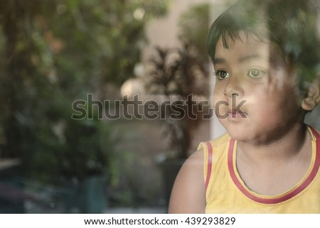 Adorable little kid boy sitting near window and looking outside. A child looks out the window. Vintage color - stock photo