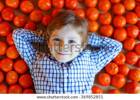 Adorable little kid boy with mandarin oranges background. Happy smiling child with lot of fruits. Healthy food, eating and lifestyle concept. - stock photo