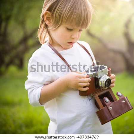 Adorable little kid boy with retro photo camera standing in the green park on s sunny day. Outdoors. Young photographer. - stock photo