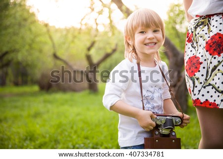 Adorable little kid boy with retro photo camera standing in the green park on s sunny day. Outdoors. Young smiling photographer. - stock photo