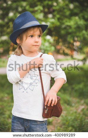 Adorable little kid boy with retro photo camera standing on a summer meadow on s sunny day. Outdoors. Young Photographer.. - stock photo