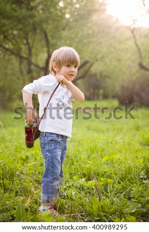 Adorable little kid boy with retro photo camera standing on a summer meadow on s sunny day. Outdoors. Young Photographer. - stock photo