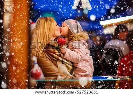 Adorable little kid daughter and young mother eating crystallized sugared apple on German Christmas market. Happy family in winter clothes with lights on background. Tradition, holiday concept