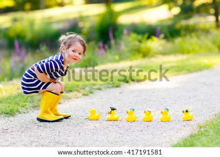 Adorable little kid girl playing in forest playground with yellow rubber ducks. Cute child wearing rain boots. Active leisure with kids. - stock photo