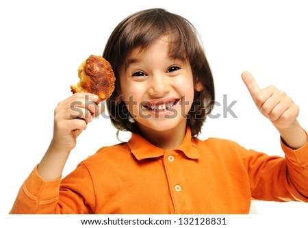 Adorable little kid holding chicken wings and show good sign - stock photo