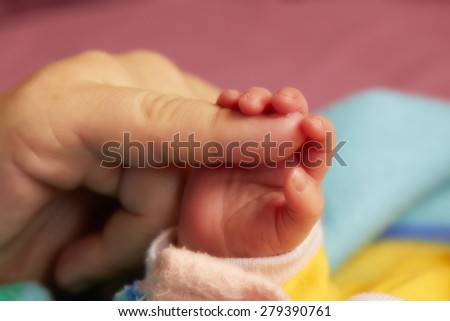 Adorable little newborn baby holding daddy's pinkie with her small hand - stock photo