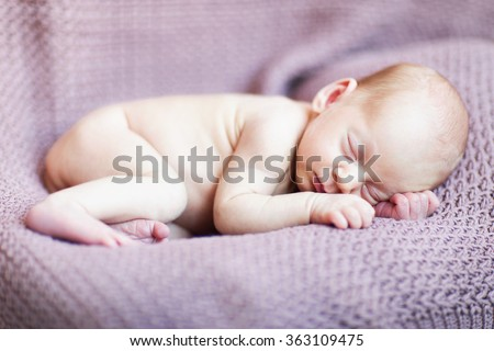 adorable little newborn boy sleeping on the brown blanket