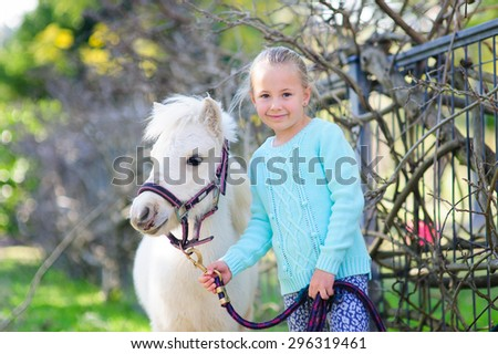 Adorable little preschool girl standing next to white pony and holding bridle in a park on a summer or spring day