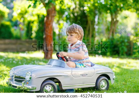 Adorable little preschool kid boy driving big toy old vintage car and having fun, outdoors. Active leisure with children during school holidays on warm summer sunny day. - stock photo