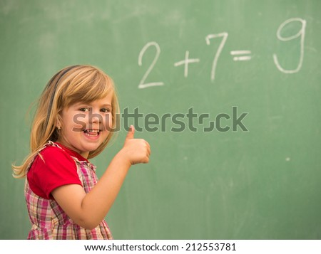 Adorable little school blonde girl in school classroom on board posing - stock photo