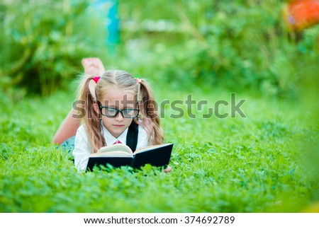 Adorable little school girl with book outdoor. Back to school  - stock photo