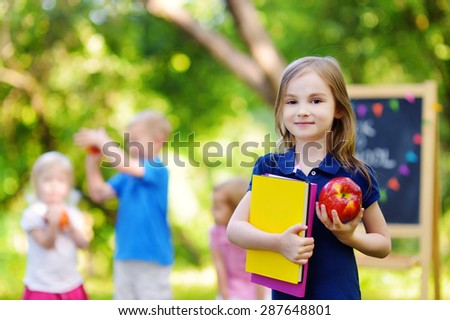 Adorable little schoolgirl feeling extremely excited about going back to school - stock photo
