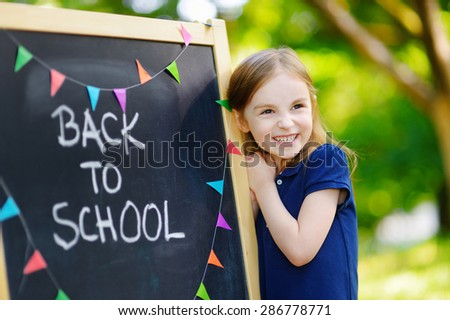 Adorable little schoolgirl feeling very excited about going back to school - stock photo