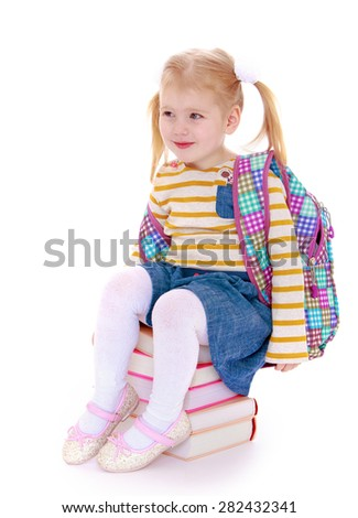 Adorable little schoolgirl sitting on a stack of books- isolated on white background - stock photo