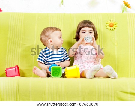 Adorable little sister and baby brother active indoors - stock photo