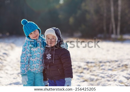 Adorable little sister and brother posing affectionately outdoors on a sunny winter's day - stock photo