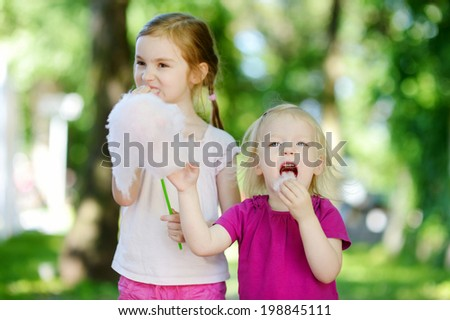 Adorable little sisters eating candy-floss outdoors at summer - stock photo