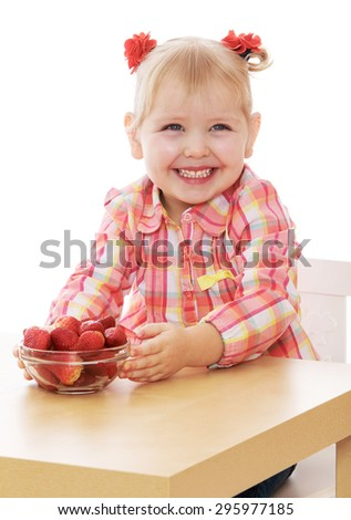 Adorable little smiling girl with small braided ponytails on her head , sitting at a table in front of her is a Cup with fresh strawberries - isolated on white background - stock photo