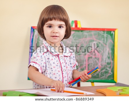 Adorable little smiling toddler girl drawing portrait