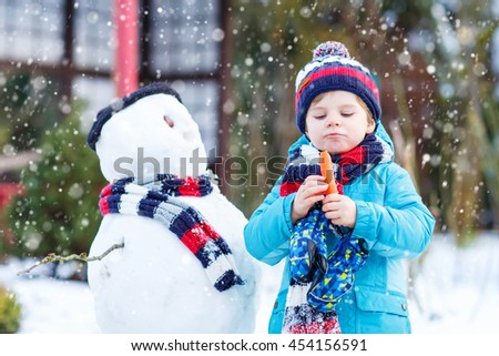 Adorable little toddler boy making a snowman and eating carrot, playing and having fun with snow, outdoors  on cold day. Active outdoors leisure with kids in winter. - stock photo