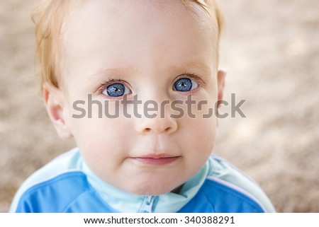 Adorable little toddler boy sitting on the  beach - stock photo