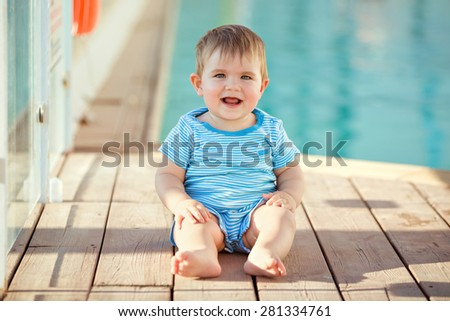 Adorable little toddler boy striped suit sitting on the background of the pool and laughs - stock photo