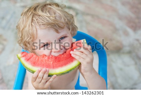 Adorable little toddler boy with blond hairs eating watermelon in summer garden - stock photo