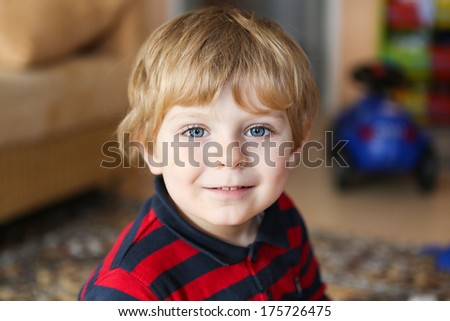 Adorable little toddler boy with blue eyes and blond hair indoor