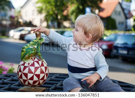 Adorable little toddler boy with handmade toy frog in summer