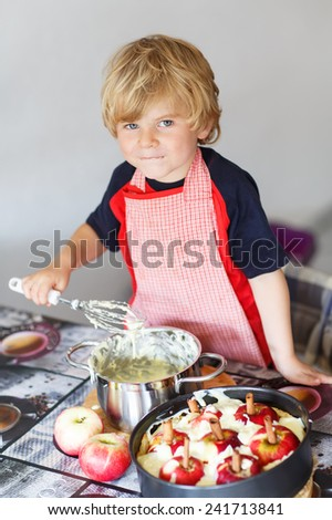 Adorable little toddler child helping and baking apple pie in home''s kitchen, indoor. - stock photo