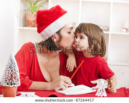 Adorable little toddler girl cuddle with her mother on Christmas eve - stock photo