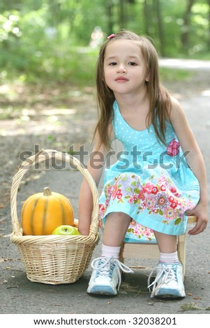 Adorable little toddler girl in a park playing with a basket with pumpkin and fruit