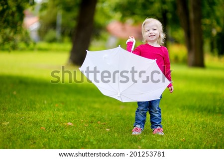 Adorable little toddler girl playing with white umbrella on warm summer day