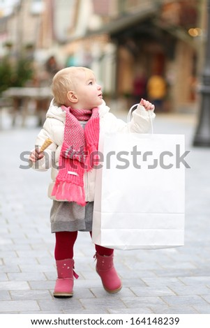 Adorable little toddler girl walking on the city street decorated with Christmas lights, carrying big white shopping bag - stock photo