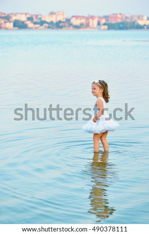 Adorable little toddler girl wearing beautiful white dress by a lake or sea on the beach in warm and sunny summer day