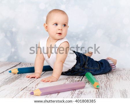 Adorable little toddler playing with big crayons - stock photo